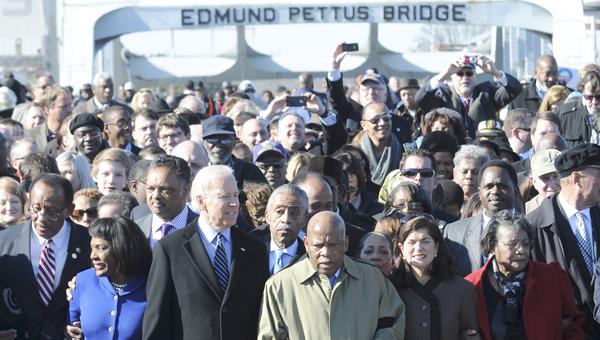 Vice President Joe Biden walks across the Edmund Pettus Bridge Sunday, locked arm-in-arm with U.S. Rep. John Lewis (D-Ga.) and U.S. Rep. Terri Sewell (D-Ala.). An estimated 15,000 took part in Sunday's bridge crossing re-enactment. -- Robert Hudson