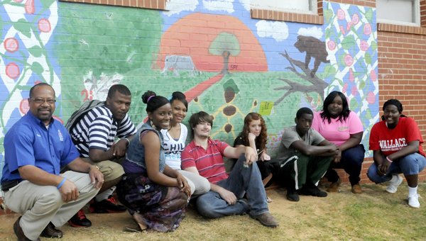 Students at Dallas County High School pose with their freshly painted mural, which resides in the school courtyard near their new outdoor classroom. Thanks to Sherwin Williams, more than $150 in paint was donated for the mural. ---Sarah Cook