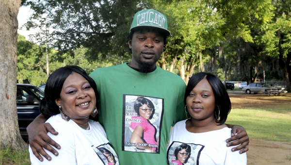 """(Left to right) Regina, Clyde and Okeemia Benjamin gather with family members at Bloch Park to remember the disappearance of Tarasha """"Pooh"""" Benjamin, their daughter and sister. --Sarah Cook"""
