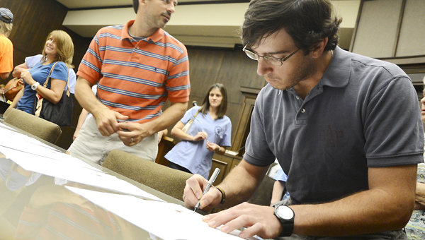 Josh Wilkerson, right, board member for the Central Alabama Animal Shelter, signs a proclamation Tuesday marking the beginnging of the week-long relationship between the Central Alabama Animal Shelter and PAWS for Hope and Faith. -- Jay Sowers