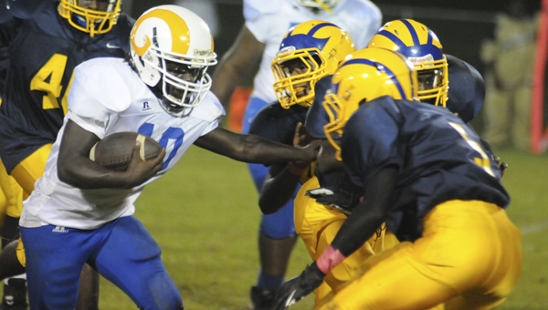 Akron running back Deontay White runs into a host of Keith defenders, including DeAnthony Griffin and Lamar Crumpton, during Friday night's game at Keith High School. --Daniel Evans