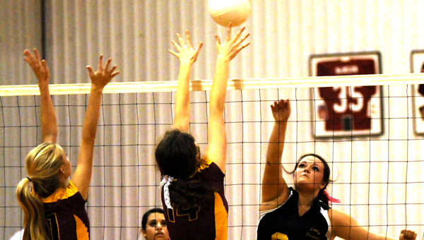 Meadowview Christian's Claudia Kendrick hits the ball just above the outstretched arms of Morgan Academy's Ashley Friday, left, Anna Kate Mock-Jordan, right, during the Trojans three sets to two victory at Morgan Academy on Tuesday night.--Daniel Evans