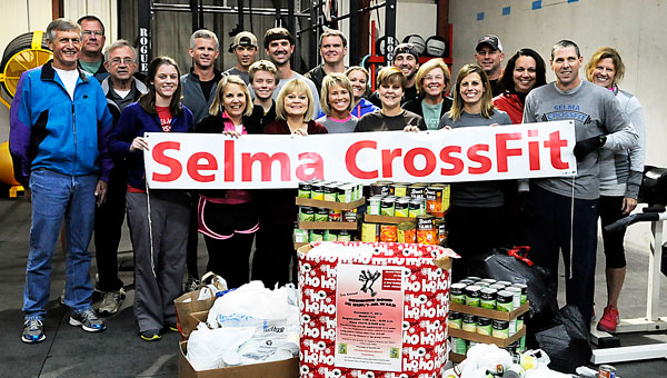 Members of Selma Crossfit donated numerous food items to the Christian Outreach Alliance Food Pantry as part of their support of the Reindeer Romp 5K and 1-mile fun run. Shown race coordinator Bill Potter (far left) are Crossfit members (front row from left) Taylor Namburo, Jill Wilkinson, Colby Whitaker, Cathy Sanders, Lisa Weber, Robin Woodson, Mary Hansell, Chelsea Chamberlain, Darien Arrington, Tommy Weber and Valerie Chittom; back row from left, Potter, George Yocum, Louis McMilion, Rick Willams, Blaze Malone, James Osborne, Mark Woodson, Megan Crane, James Roberts and Reid McMilion. (Dennis Palmer / Times-Journal)