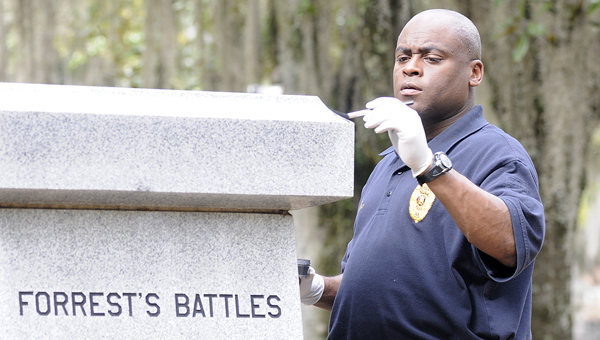 The spark: Selma Police Department's Sgt. Tori Neely dusts for prints in March 2012 after the bronze bust of Nathan Bedford Forrest was stolen from the monument that is placed in Old Live Oak Cemetery.  This theft is what led to monument sponsors to lead efforts to build a bigger monument, which drew protests and ultimately led to a lawsuit after the city of Selma shut down construction efforts. -- File Photo
