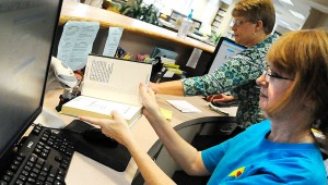 Christine Grant scans a returned book in Tuesday afternoon at the Selma-Dallas County Public Library.  (Jay Sowers | Times-Journal)