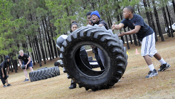 Army recruits preparing for basic training, flip a tire while holding a medicine ball Friday at Selma Crossfit on Landline Road. -- Josh Bergeron