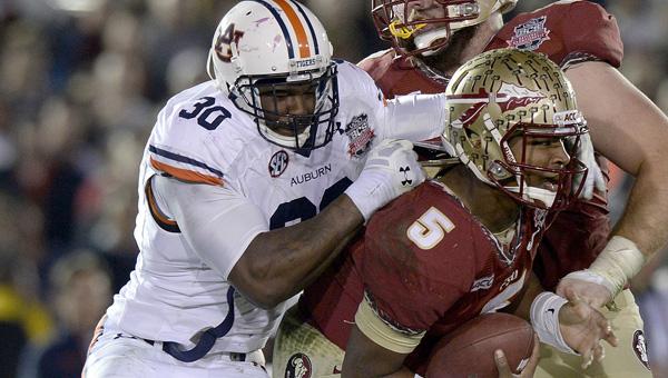 Tough to bring down: Auburn's defensive lineman Dee Ford (30) brings down Florida State's quarterback Jameis Winston during Monday's BCS National Championship game in Pasadena, Calif.  The Seminoles defeated Auburn 34-31. -- Todd Van Ernst | Auburn University