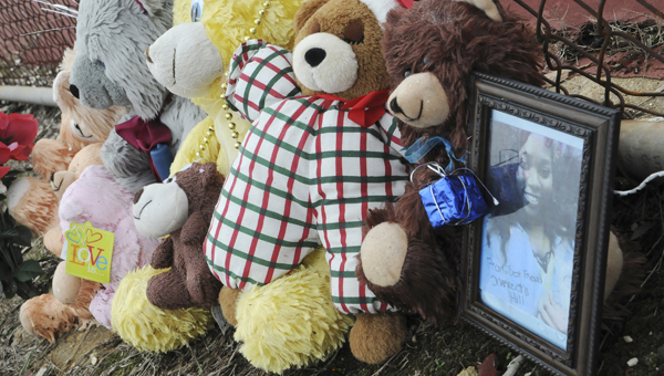 Far too young: Stuffed animals, photos, flowers and candles sit along the outside of the fence surrounding Selma High School's tennis court as a makeshift memorial to Alexis Hunter who was killed just days before Christmas. --Sarah Robinson