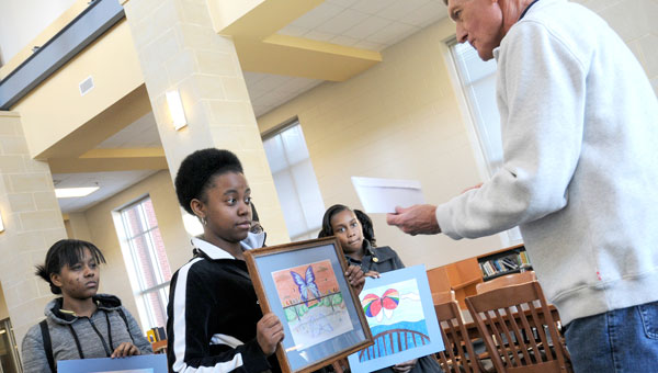 Selma High senior Aliyah Peterson receives $100 in prize money after being named the overall best in the Butterflies and Bridges Art Competition. (Jay Sowers | Times-Journal)