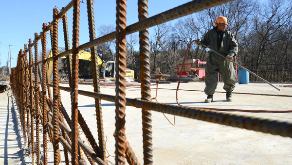 Yancy Collins uses an air hose to blow dirt and debris from the deck of the bridge under construction on Dallas Avenue Wednesday afternoon. (Jay Sowers   Times-Journal)