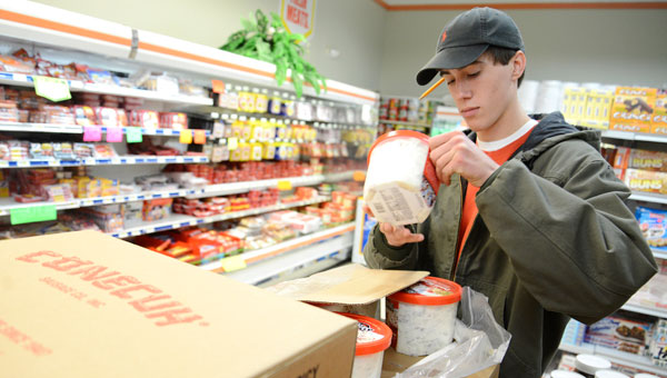 Dave's Market employee Parker Duke unloads boxes of foods while stocking the shelves at Dave's Market in Valley Grande on Monday afternoon. Store owner David Oliver said his store has increased their orders of milk, eggs and bread by 25 percent in preparation for Tuesday's snowfall. (Jay Sowers | Times-Journal)