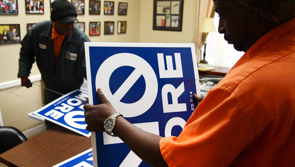 Selma Public Works employees Lee Barnes, left, and Marvin Lewis work together to assemble non-violence signs displaying the message 'NO MORE' on Thursday morning at City Hall. MAyor George Evans purcahsed the signs, and he has invited the public to display them around town. (Jay Sowers | Times-Journal)