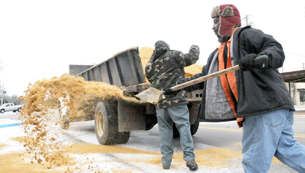 Selma Public Works employee Marvin Lewis spreads sand over the roads near the St. James Hotel one day after a snow storm rolled through Selma. (Josh Bergeron | Times-Journal)