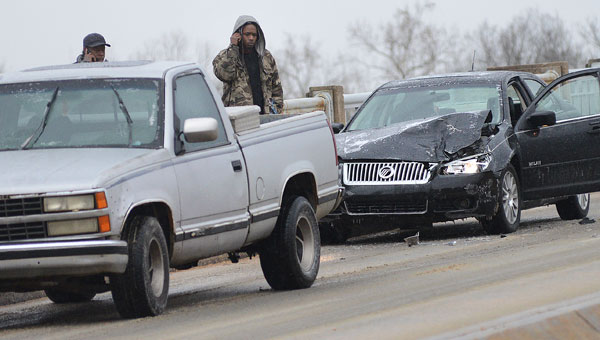 Two motorists look over the damage to their vehicles following an accident Tuesday morning on the  Edmund Pettus Bridge.  State highway crews worked throughout Tuesday trying to keep sand on the bridge to prevent a build up of ice. (Jay Sowers | Times-Journal)