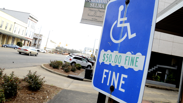 A sign clearly marks one of the handicap parking spots located on Broad Street in downtown Selma.  The sign also shows the monetary penality that could be levied against those who use the parking spot who are not handicap.  Selma Police officials have said they intend to step up patrols to enforce handicap parking, as well as other parking violations.--Jay Sowers