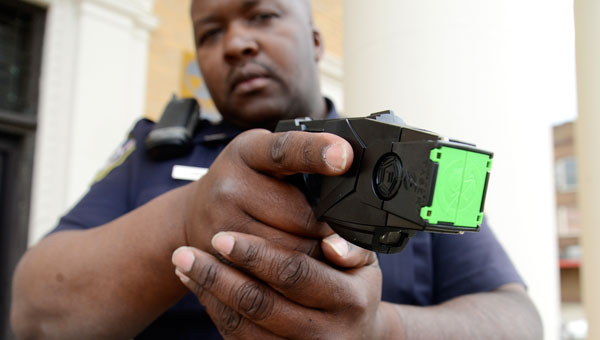 Selma Police Department Officer Nathan Gibson aims one of the 27 new tasers the department received earlier this month. (Jay Sowers | Times-Journal)