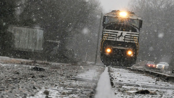 A Norfolk Southern train moves slowly down a track  during severe snowfall in Selma last week. (Josh Bergeron | Times-Journal)