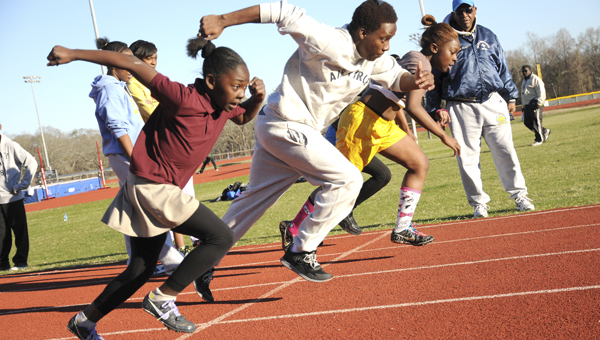 Rashna Walker, left,  a member of Walker Track Club, takes off from the starting line against member of the Selma High Track Team Thursday during practice at Memorial Stadium.--Josh Bergeron