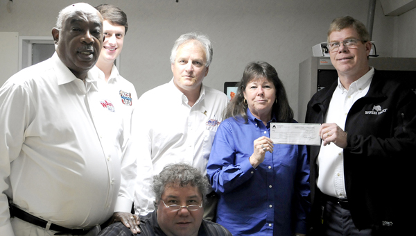 Bush Hog customer represenative Karen Peacock and Bush Hog Human Resources Manager David Middlebrooks, far left, hold a $1,000 check for the St. Jude Organization Wednesday at KIX Country Radio during a radiothon meant to raise money for the hospital. From left to right, KIX Country Station manager Wayne Sharpe, station president Paul Alexander, station CEO Scott Alexander are picture with operations manager Todd Prater kneeled in front of the group. (Sarah Robinson | Times-Journal)