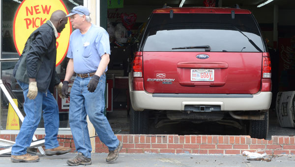 Workers clear glass, metal and other debris from around an SUV that had been driven in to the front of Selma's Calhoun Foods grocery store on Tuesday afternoon. (Jay Sowers   Times-Journal)