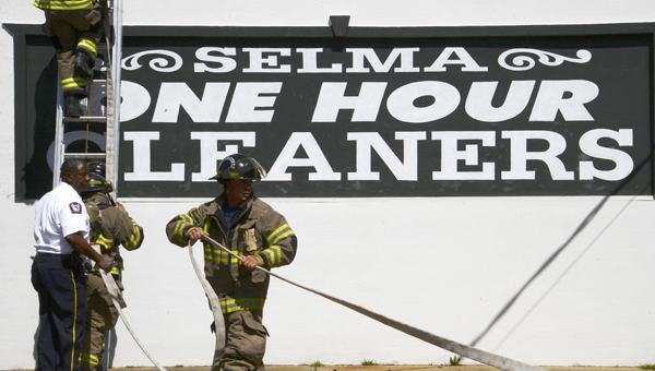 Members of the Selma Fire Department head on to the roof of the Selma One Hour Cleaners laundry location Monday morning after a fire started in a dryer vent at the business. (Jay Sowers | Times-Journal)