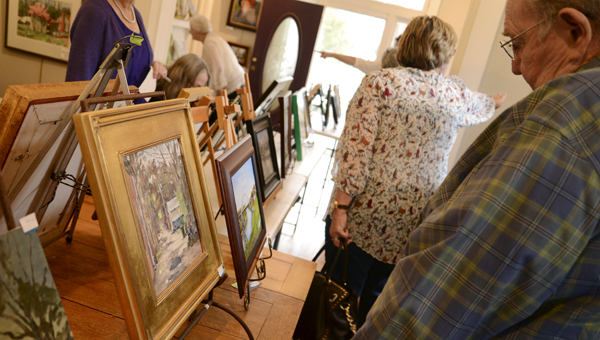 Art lovers at the Selma Art Guild look over the artwork created by plein air artists. -- Jay Sowers