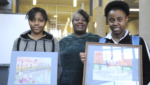 Selma High students Sierra Sanders (left) and Aliyah Peterson (right) show off their artwork on Thursday after winning the Butterflies and Bridges Art Contest. (Josh Bergeron | Times-Journal)