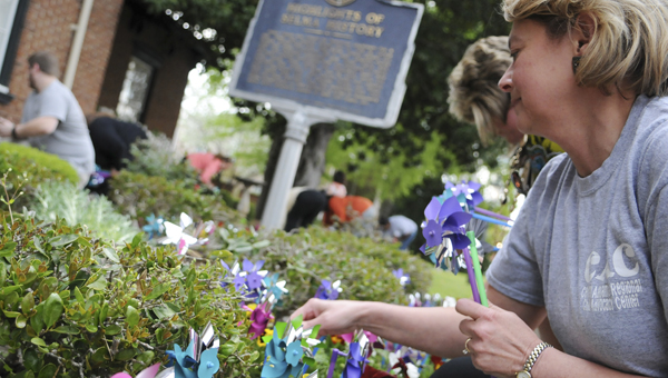 Josh Bergeron | Times-Journal Decorating for a cause: Jan Justice, who works at the Dallas County Family Resource Center, places pinwheels in front of Selma's City Hall on Tuesday. Dozens of people placed 305 pinwheels in front of city hall to represent the reported cases of child abuse in Dallas County in 2013. The event is a part of child abuse prevention month.
