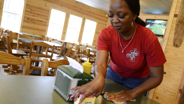 Brenda Purifoy wipes down a table at the Sandbar restaurant Friday afternoon. The restaurant is scheduled to reopen for business at 11 a.m. Saturday morning after being closed for a week-and-a-half due to flood damage. (Jay Sowers | Times-Journal)