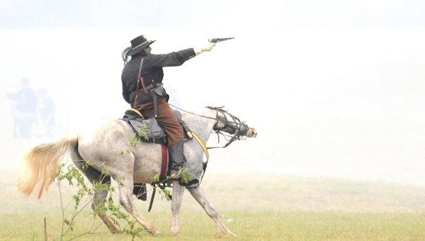 A confederate calvary solider fires a pistol at union troops Sunday during the Battle of Selma re-enactment. (Josh Bergeron | Times-Journal)