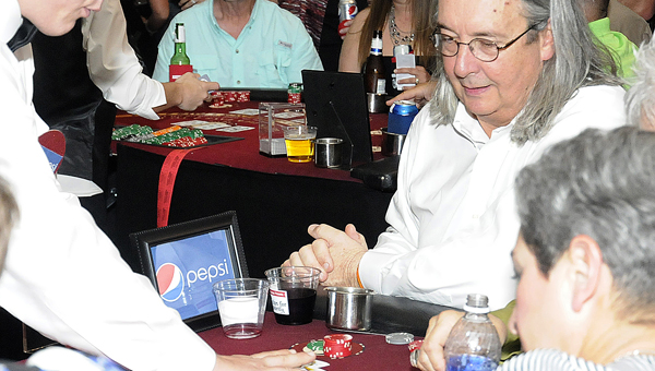 John Pilcher, right, talks to dealer Royal Boswell, left, during the Selma Chartiy League;s second annual Chips for Charity fundraiser Saturday night at the Old National Guard Armory.