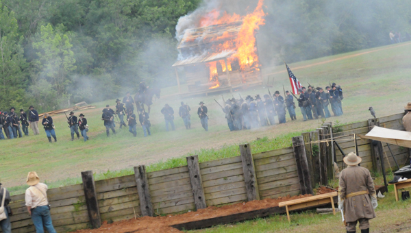 After burning a wooden cabin, union soldiers advance as Confederate commander Gen. Ken Sumner looks on. This year marked the 149th anniversary of the Battle of Selma, fought in April 1865. (Josh Bergeron | Times-Journal)