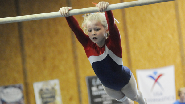 Madilyn Stevens, left, walks on the balance beam at the Dixie Flips Fun Meet on Saturday.. Sarah Lloyd Free, top right, swings from the bars during Saturday's gymnastics meet.  Evey Craig,  bottom right, performs her floor routine.--Daniel Evans