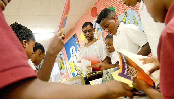 Knox Elementary School librarian Tracy Woods, center, looks on as students dig through a pile of newly donated books Tuesday morning. (Jay Sowers | Times-Journal)