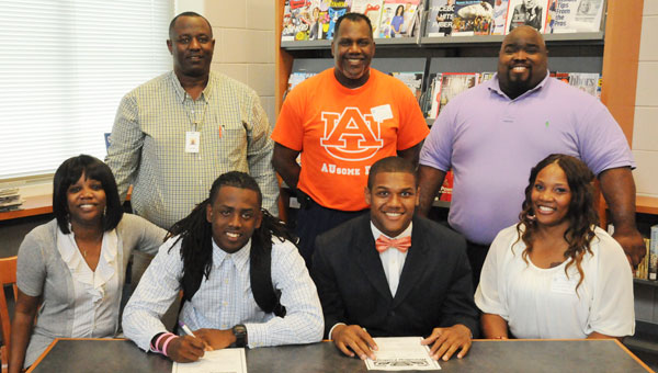 Selma's Adam Bruno, center left, and Kendell Smith, center right, smile after signing their letters of intent to play college football with Reedley College in California.  In the front row (left to right) is T'schenavia Strong, Bruno's mother, Bruno, Smith, and Juanita Knox, Smith's mother. In the back row are (left to right) Selma head football coach Leroy Miles, Pastor Curtis Jackson and Saints' assistant football coach Robert Wilkerson. (Daniel Evans | Times-Journal)