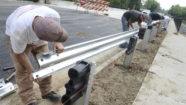 Michael Hartley, left, holds up a section of guardrail while it is installed near the Dallas Avenue bridge project late Tuesday morning. -- Jay Sowers