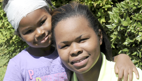 Selma residents Ja'Terrika Thomas, 4, left, and Caroline Thomas, her mother, right, pose for the camera Wednesday outside of their home on 2100 block of Lauderdale Street. Ja'Terrika was allegedly  attacked by the neighbor's pit bull Friday. (Sarah Robinson | Times-Journal)