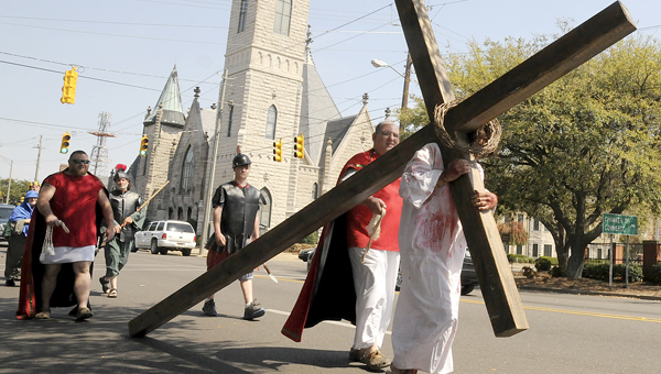 A different path: A process depicting Christ carrying the cross winds its way through Selma's downtown last year.  This year's procession will have to travel a different route because of bridge construction on Dallas Avenue. (File Photo   Times-Journal)