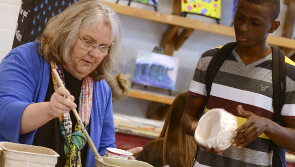 Dallas County High School art teacher Jo Taylor, left, works with a student on a pottery project during class last week. -- Jay Sowers