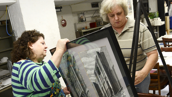 Candi Duncan, left, and Cindy Stoudenmire place two drawings Stoudenmire did of the front of Selma's old YMCA building on display Thursday at the Dallas Academy Building. (Jay Sowers | Times-Journal)