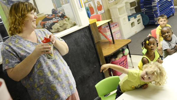 Pre-kindergarten teacher Shannon Duncan, left, laughs with a classroom of students Thurday morning at Little People Daycare. (Jay Sowers | Times-Journal)