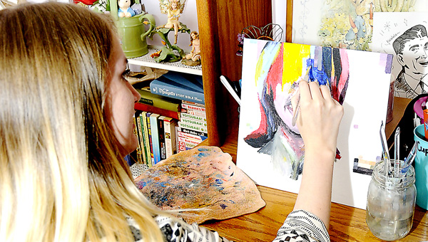great work: Hannah Murray sits at her desk, cluttered with some of her other art pieces, and works on her latest painting. -- Sarah Robinson