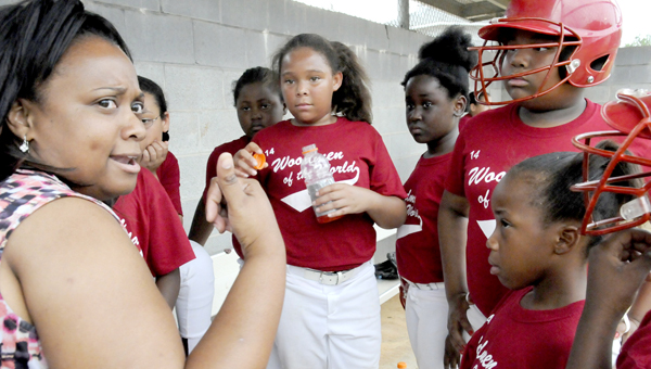 Taurus Smith, a team mom for Woodmen of the World, gives the girls a pep talk in between innings after the Woodmen of the World allowed several runs from their opponent. (Scottie Brown   Times-Journal)