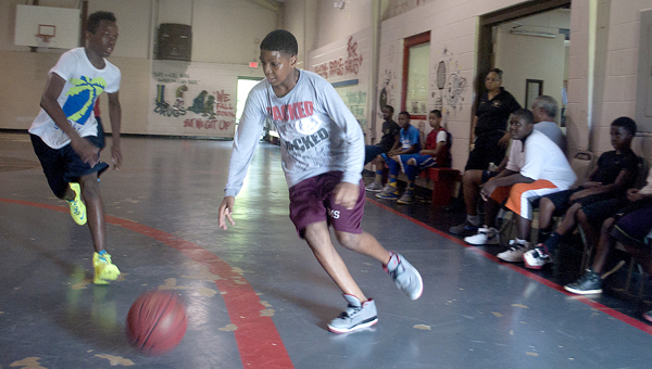 Cedric Hunter dribbles toward the lane as Jacquez Wright defends during a pickup game at the Police Athletic League gym in Selma. (Christopher Edmunds | Times-Journal)
