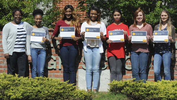 Dallas High County High School business teacher Dorothy Moore, left, poses for the camera Tuesday next to six of the more than 30 students that have earned a Microsoft Office Specialist Certification as part of Alabama's Microsoft IT Academy program. Pictured from left to right are Moore and Dallas High juniors Laquesha White, Hadiyyah Lane, Nicole Stewart, Kayla Graves, Alanna Salter and Emily Morgan. (Sarah Robinson | Times-Journal)