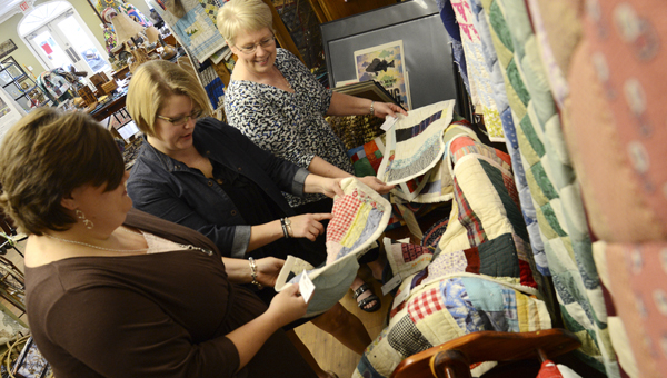 Jennifer Smith, Kristin Law and Sulynn Creswell look over quilts made by loacl artists Thursday at the Blackbelt Treasures Cultural Arts Center in Camden. -- Jay Sowers