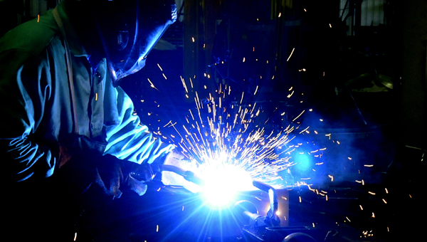 A welder at Bush Hog lights up the production area while completing one of the company's well-known products.  Bush Hog, which faced significant job losses in the past, is making a comeback and adding jobs. -- File Photo
