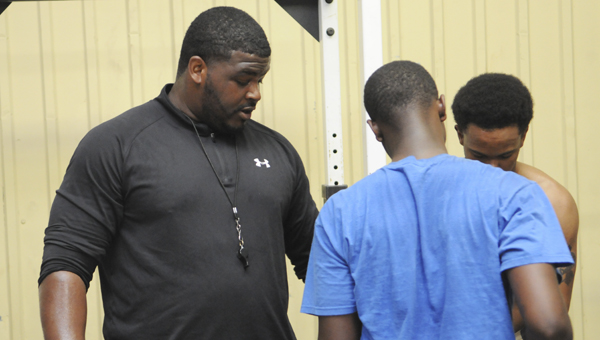 Ellwood Christian football coach Eric Martinear,  left, talks to his players during a weight lifting session Wednesday afternoon. Martinear was hired as the Eagles new football coach after a month-long search. He played college football at Lane College and played in the IFL with the New Mexico Stars.--Daniel Evans