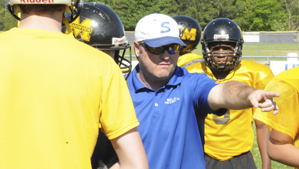 Above, Meadowview Christian head coach Lebo Jones, center, talks to his players during practice. Below, Meadowview Christian's Timmy Hall, pitches the ball as the Trojans' practice running the option.--Daniel Evans