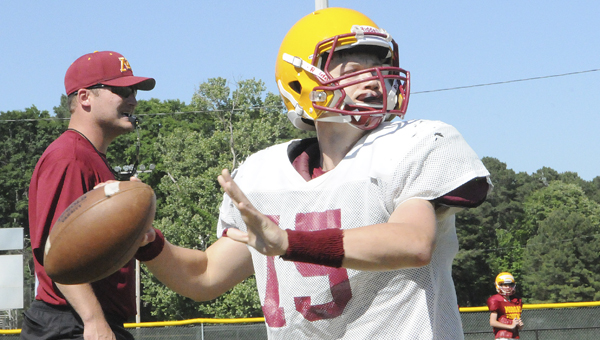 Morgan Academy quarterback Harrison Adams, above, throws the football as head coach Jake Wingo looks on during Tuesday's practice. Wingo, below, watches a group of offensive lineman step through a drill. --Daniel Evans